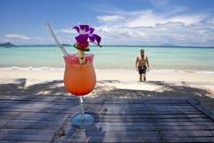 Uomo con il cocktail alla spiaggia. Fotografie Stock
