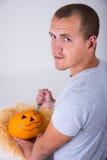 Uomo con il coltello che scolpisce la Jack-O-lanterna della zucca per Halloween Immagine Stock Libera da Diritti