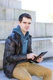 Uomo con il computer della compressa che esamina la macchina fotografica, all'aperto. Immagine Stock Libera da Diritti