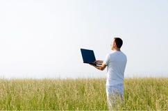 Uomo con il computer nel campo. Immagini Stock Libere da Diritti