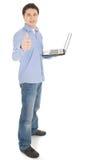 Uomo con il computer portatile che mostra i pollici in su Immagini Stock