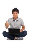 Uomo con il computer portatile che mostra i pollici in su Immagine Stock