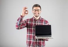 Uomo con il computer portatile che mostra segno GIUSTO Fotografia Stock Libera da Diritti