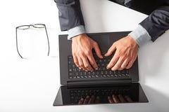 Uomo con il computer portatile che scrive sulla tastiera Sulla tabella bianca fotografia stock