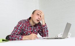 Uomo con il computer portatile che sembra sollecitato Fotografie Stock Libere da Diritti