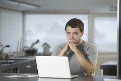 Uomo con il computer portatile che si siede al contatore di cucina Fotografie Stock