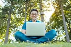 Uomo con il computer portatile che si siede all'aperto in natura Fotografie Stock Libere da Diritti