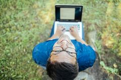 Uomo con il computer portatile che si siede all'aperto in natura Immagine Stock