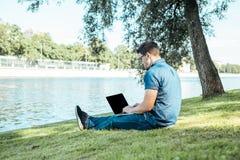 Uomo con il computer portatile che si siede all'aperto in natura Immagini Stock