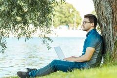 Uomo con il computer portatile che si siede all'aperto in natura Immagine Stock Libera da Diritti