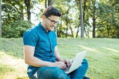 Uomo con il computer portatile che si siede all'aperto in natura Fotografie Stock