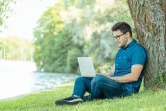 Uomo con il computer portatile che si siede all'aperto in natura Fotografia Stock Libera da Diritti
