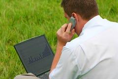 Uomo con il computer portatile che si siede nell'erba immagine stock libera da diritti