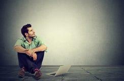 Uomo con il computer portatile che si siede su un fantasticare di pianificazione di pavimento Fotografie Stock Libere da Diritti