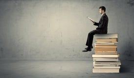 Uomo con il computer portatile che si siede sui libri Immagine Stock