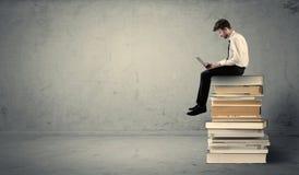Uomo con il computer portatile che si siede sui libri Fotografia Stock