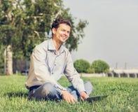 Uomo con il computer portatile che si siede sul prato inglese verde Fotografie Stock Libere da Diritti