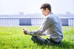Uomo con il computer portatile che si siede sul prato inglese verde in parco Fotografie Stock Libere da Diritti