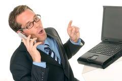 Uomo con il computer portatile del calcolatore sul suo telefono delle cellule Immagini Stock