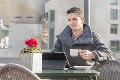 Uomo con il computer portatile della tazza di caffè nel ristorante del terrazzo. Fotografie Stock