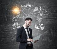 Uomo con il computer portatile e la bolla di affari Fotografia Stock