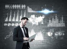 Uomo con il computer portatile e sei grafici sulla lavagna Immagine Stock