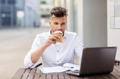 Uomo con il computer portatile ed il caffè al caffè della città Fotografie Stock