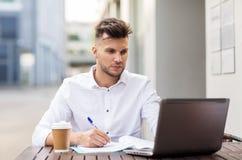 Uomo con il computer portatile ed il caffè al caffè della città Immagine Stock