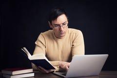 Uomo con il computer portatile ed il libro Fotografie Stock
