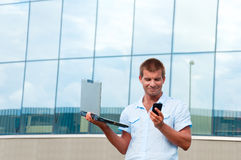 uomo con il computer portatile ed il telefono cellulare davanti alla costruzione moderna di affari Immagine Stock
