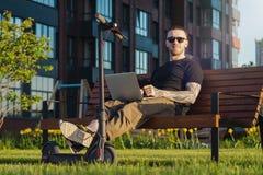 Uomo con il computer portatile ed il motorino elettrico moderno di scossa che si siedono al parco contemporaneo fotografia stock