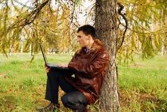 Uomo con il computer portatile esterno. Fotografia Stock