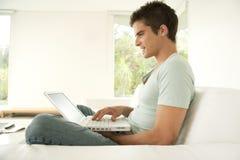 Uomo con il computer portatile nel paese Immagine Stock