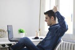 Uomo con il computer portatile nella stanza Immagine Stock