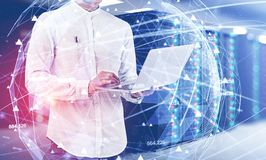 Uomo con il computer portatile nella stanza del server, concetto della rete fotografie stock