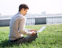 Uomo con il computer portatile OM il prato inglese verde nella città Fotografia Stock