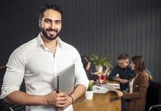 Uomo con il computer portatile prima del gruppo immagine stock libera da diritti