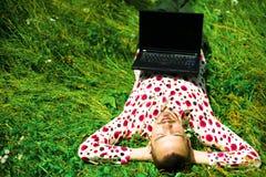 Uomo con il computer portatile su erba Fotografia Stock Libera da Diritti