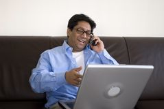 Uomo con il computer portatile sul telefono fotografia stock libera da diritti