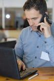 Uomo con il computer portatile in ufficio Fotografia Stock Libera da Diritti