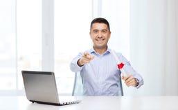 Uomo con il diploma ed il computer portatile che indica dito Fotografia Stock Libera da Diritti