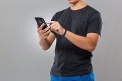 Uomo con il dispositivo e l'uso astuti del telefono cellulare Fotografia Stock