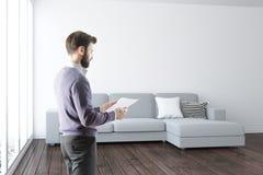Uomo con il documento in salone Fotografia Stock
