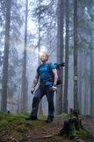 Uomo con il faro e lo zaino nella foresta immagine stock