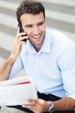 Uomo con il giornale ed il telefono cellulare fotografia stock libera da diritti
