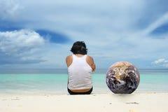 Uomo con il globo che si siede sulla spiaggia Fotografia Stock