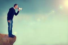 Uomo con il megafono che grida dal bordo della scogliera Fotografie Stock Libere da Diritti