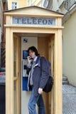 Uomo con il microtelefono nel callbox della via. immagini stock