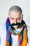Uomo con il moustache falso e la sciarpa colorata Fotografie Stock Libere da Diritti
