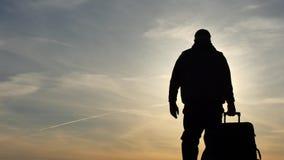 Uomo con il movimento lento della siluetta della valigia isolato con il fondo del cielo stock footage